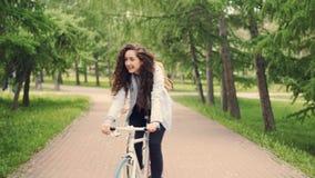 移动式摄影车在公园,看和笑的射击了愉快的女学生朋友骑自行车 美丽的树和草坪 影视素材