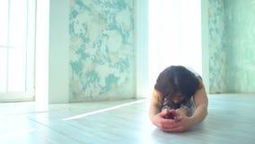 移动式摄影车在家被射击在窗口前面的女子实践的瑜伽 女性做的瑜伽在有自然光的一个演播室 股票视频