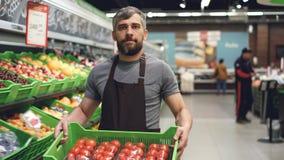 移动式摄影车射击了围裙运载的箱的年轻推销员蕃茄在水果和蔬菜部门的超级市场 股票录像