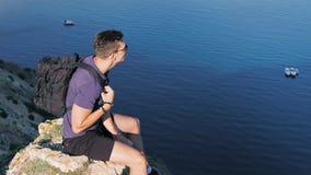 移动式摄影车射击了男性背包徒步旅行者极端坐看在大角度下的峭壁 股票视频