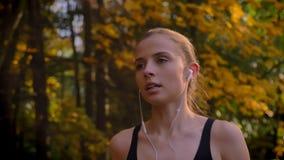 移动式摄影车射击,跑在有耳机的秋季公园的年轻可爱的白种人亭亭玉立的女孩特写镜头画象  影视素材