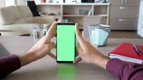 移动式摄影车浏览在有绿色屏幕色度嘲笑的智能手机的男性手滑子射击  股票录像