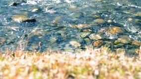 移动式摄影车滑子射击了飞溅的水在山河在森林湿岩石和太阳光芒附近 水平平稳 股票录像