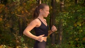 移动式摄影车被射击去跑步在秋季公园的连衫裤的年轻亭亭玉立的女孩 股票录像