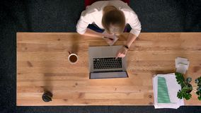 移动式摄影车被射击在工作和做笔记的观点的上面的偶然穿戴的妇女下在膝上型计算机前面的办公室 股票视频