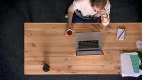 移动式摄影车被射击在观点的上面的偶然穿戴的妇女下谈话在手机和饮用的咖啡在前面的办公室 影视素材