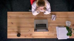 移动式摄影车被射击在观点的上面的正式穿戴的妇女下谈话在手机在膝上型计算机前面的办公室 影视素材