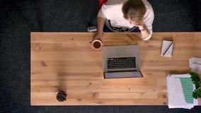 移动式摄影车被射击在观看入膝上型计算机的屏幕的观点的上面的偶然穿戴的妇女下,饮用的咖啡在办公室 股票视频