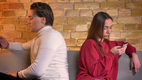 移动式摄影车被射击年轻白种人夫妇紧接坐有智能手机的沙发在家庭环境 股票录像
