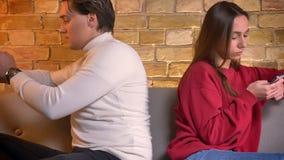 移动式摄影车被射击年轻白种人男人和妇女紧接坐有智能手机的沙发在家庭环境 股票录像