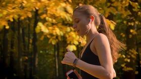 移动式摄影车跑在有电话和耳机的秋季公园的被射击年轻可爱的白种人亭亭玉立的女孩 股票录像