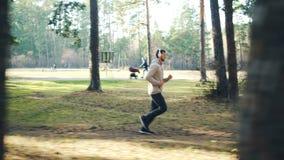 移动式摄影车跑步在公园和听到音乐的被射击田径服的有胡子的年轻人和运动鞋通过现代 股票录像