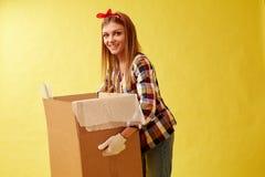 移动新的地方和修理概念-年轻女人的人们拿着纸板箱 黄色背景 免版税图库摄影