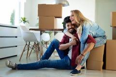 移动新的家和打开carboard箱子的年轻夫妇 免版税库存图片