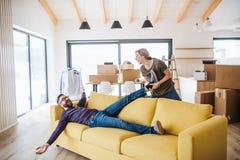 移动新的家的一对年轻夫妇,获得乐趣 免版税库存图片