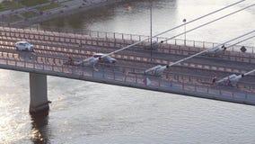 移动沿在维斯瓦河,华沙的现代guyed桥梁的骑自行车者和汽车空中射击  库存照片