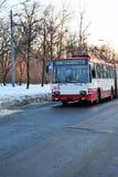 移动沿多雪的公园,冬天的老红色和白色台车 库存图片