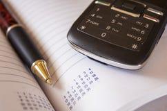 移动电话和笔 免版税库存图片