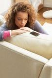 移动电话坐的沙发wating的妇女 免版税库存照片