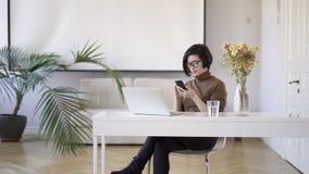 移动电话的亚裔妇女坐在白色家庭办公室
