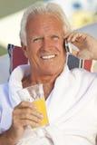 移动电话的前辈喝橙汁的 库存图片