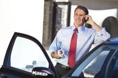 移动电话的生意人或建筑师乘Car 库存照片