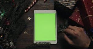 移动男性的手,轻拍,在白色片剂计算机上的迅速移动的页有绿色屏幕的 特写镜头 顶视图 股票录像