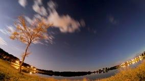 移动的云彩和星在湖上在晚上,飞旋镖timelapse 股票视频