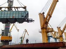 移动的在口岸的货物火车由口岸起重机 货物举的操作 行业端口 免版税库存图片