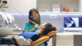 移动的射击在牙医办公室,审查和工作在患者牙的一位年轻女性牙医,射击移动 股票视频