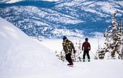 移动的年轻挡雪板神色在观光的滑雪者附近 免版税库存图片