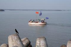移动通过在江苏瓷的水的小船与在打桩的鸟在前景 库存照片