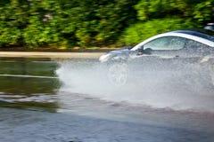 移动通过水坑的汽车 图库摄影