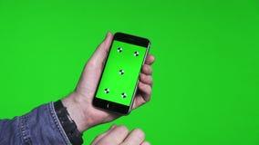 移动页的人的手使用有绿色屏幕的电话 影视素材