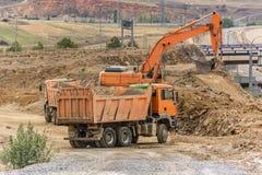 移动高速公路的建筑的卡车和挖掘机地球 库存图片
