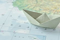 移民和请求收容所概念-在地图的纸小船 库存照片