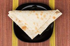 稀薄的亚美尼亚lavash被折叠的三角在黑色的盘子的在席子 免版税库存图片