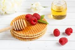 稀薄的比利时华夫饼干用蜂蜜和莓 茉莉花花和一个瓶子在轻的木背景的蜂蜜 库存图片