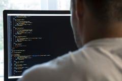 程序员从在计算机显示器的后面和编程的代码 库存图片