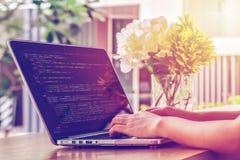程序员` s特写镜头在一个夏日递研究在一台膝上型计算机的原始代码 免版税库存图片
