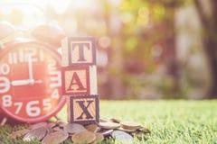 税在颜色字母表木箱子写在堆泰铢硬币 图库摄影
