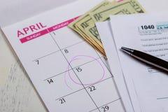 税天、美元和形式1040所得税形式陈列税天4月日历的与词 免版税库存照片