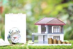 税时间概念,有堆积的硬币金钱和闹钟和日历式样房子在自然绿色背景 免版税库存图片