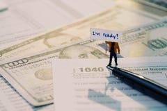 税概念,拿着标志I& x27的微型小雕象的时刻; 准备好的m 免版税库存图片