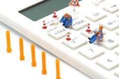 税演算的微型人建筑工人键盘税按钮 容易计算 在白色backgr的白色计算器上 免版税库存图片