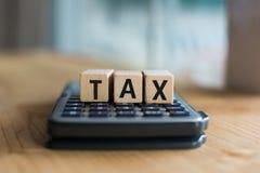 税的词拼写了与五颜六色的木字母表块 选择聚焦,浅景深 免版税库存图片