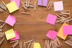 稠粘的笔记和颜色铅笔在木书桌上 免版税库存照片