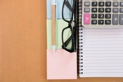 稠粘的笔记,计算器,圆珠笔,空的笔记本,在办公桌上的镜片 事务,会计概念 与警察的顶视图 库存图片