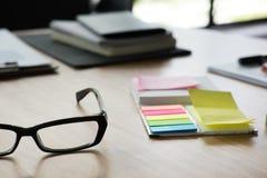 稠粘的笔记,镜片,在办公桌上的笔记本 事务,工作 库存照片