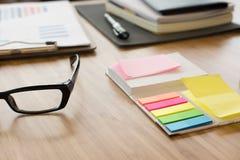稠粘的笔记,镜片,在办公桌上的笔记本 事务,工作 免版税库存照片